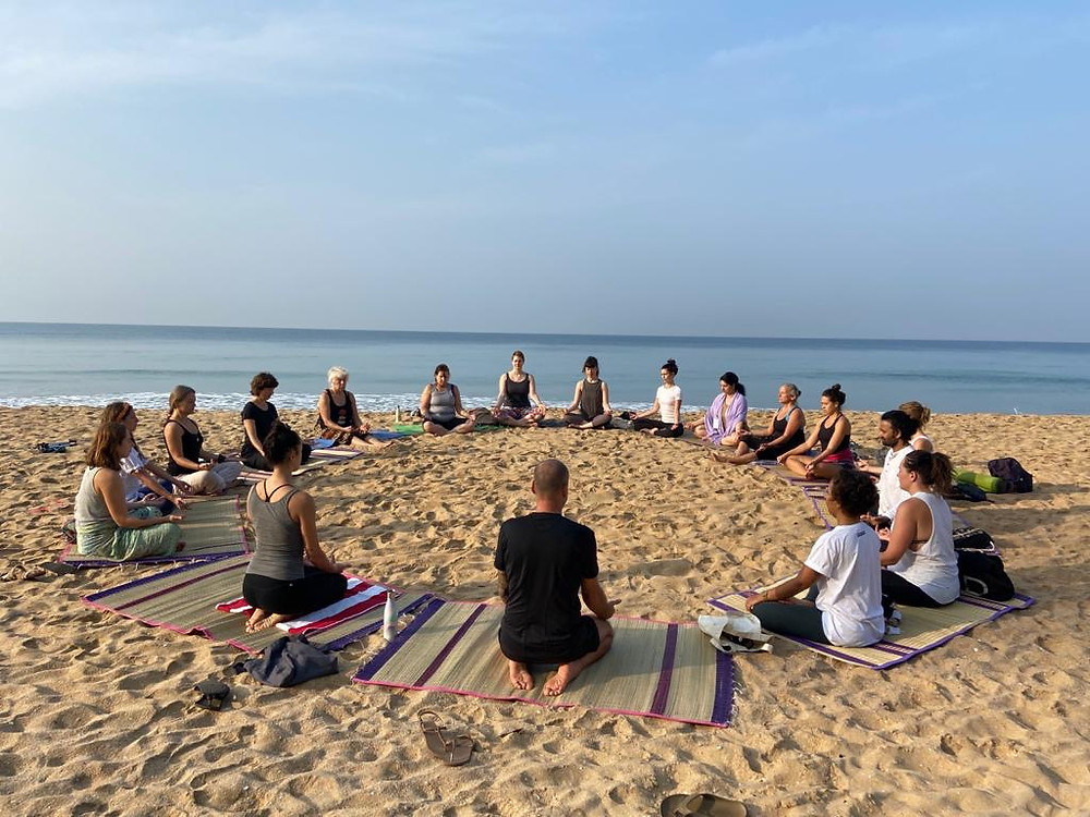 Group doing yoga and meditation at the beach