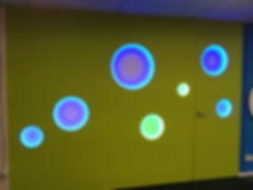 Lit perspex disks in office wall