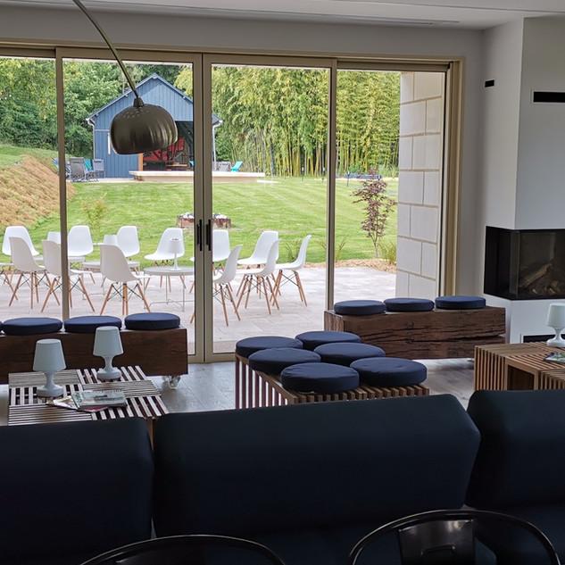 Salon et cheminée vue sur terrasse et piscine
