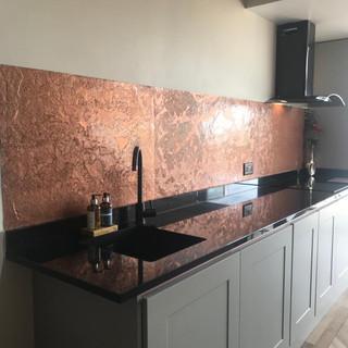 Copper metal veneer kitchen wall.