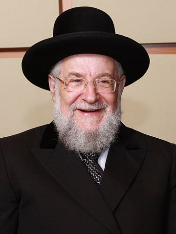 Profile shot of Rabbi Yisroel Meir Lau wearing a black coat and tie and a black hat