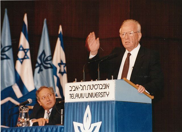 """Yitzhak Rabin standing at a podium which reads """"Tel Aviv University"""" with his hand raised"""