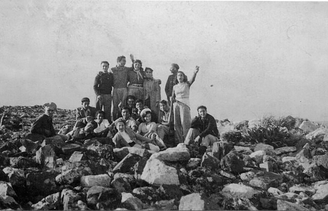 A group of young Palmah fighters, half standing, half sitting on large rocks in a group photo