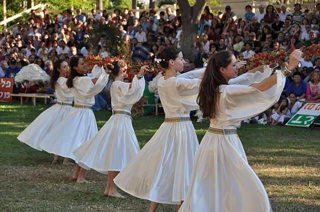 5 girls wearing white dresses and dancing in a row in front of a crowd in bleachers