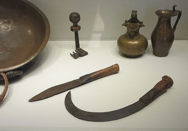 A sickle and knife behind a display case in a museum