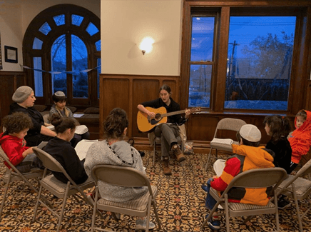 Tamar Segal playing the guitar for children during her gap year abroad