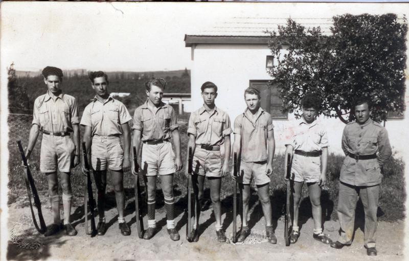 6 young men with guns lined up with their counselor at the end of the row