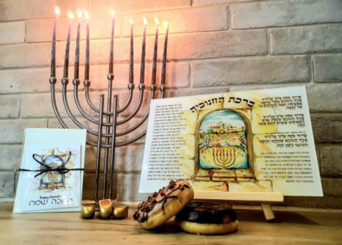 A Hanukkah blessing card with a hanukkiah and doughnuts on a table by Art & Ketubot by Rena