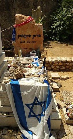The headstone of Israeli singer Arik Einstein covered in an Israeli flag and stones