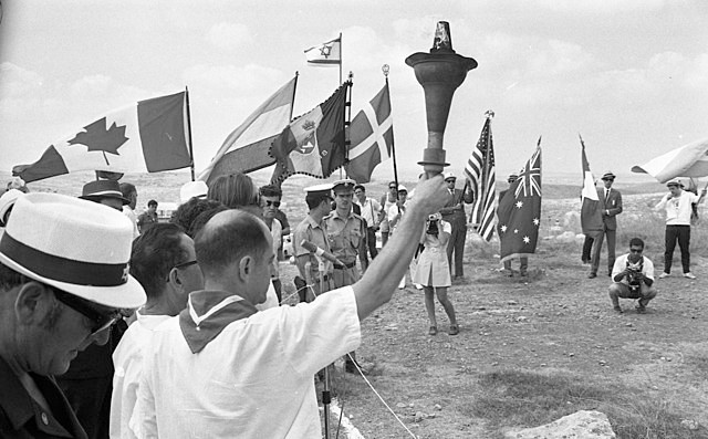 Lighting the 8th Maccabiah torch at the Tombs of Maccabees with flags from various countries