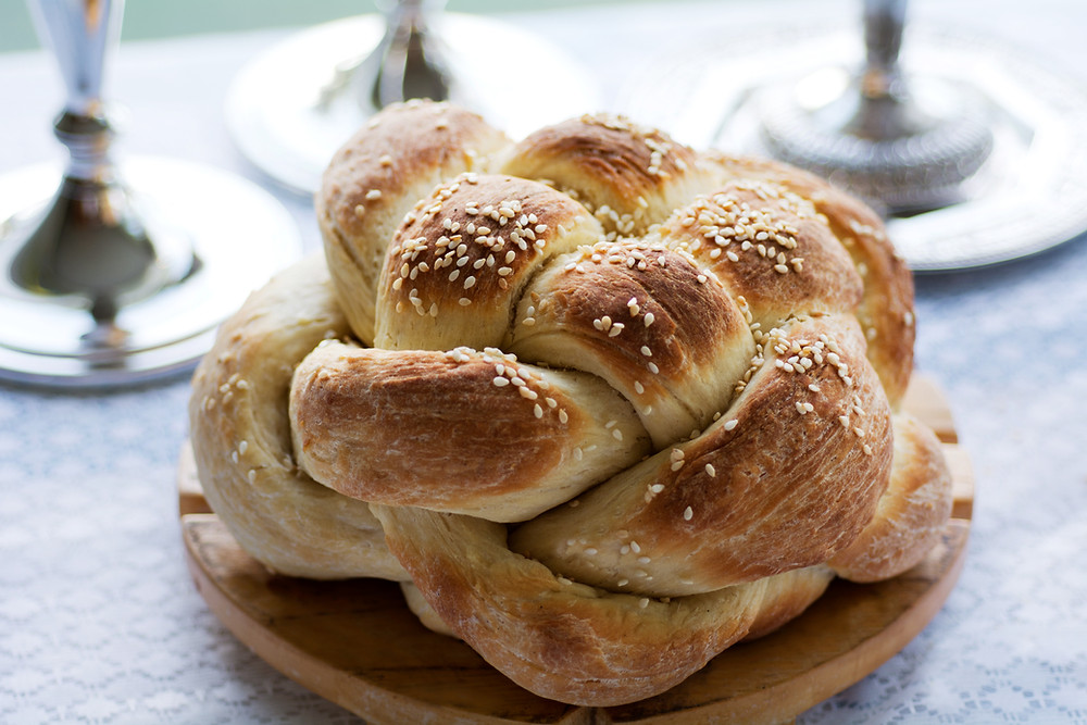 A round, braided Challah for Shabbal on a wooden board