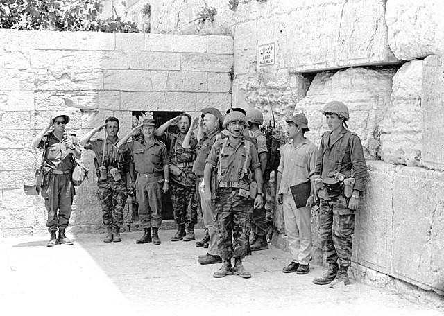Israeli soldiers in 1967 standing next to the Western Wall after its liberation with their hands raised to their heads singing HaTikva,
