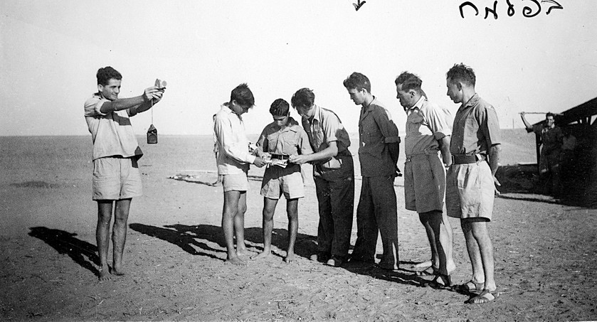 7 men in the Palmah standing around one man who is teaching navigation outside