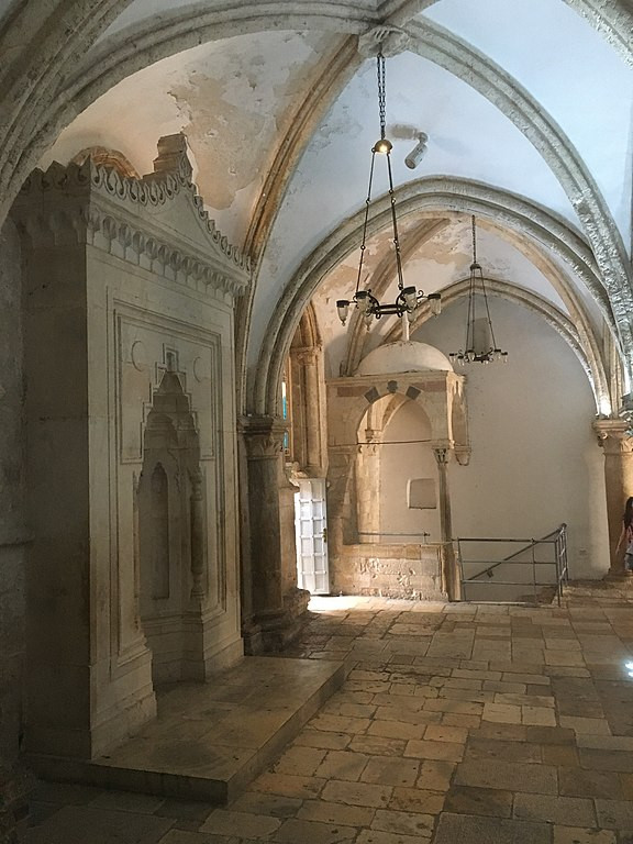 Inside the Cenacle with a stone structure on the left and a staircase at the far end of the room