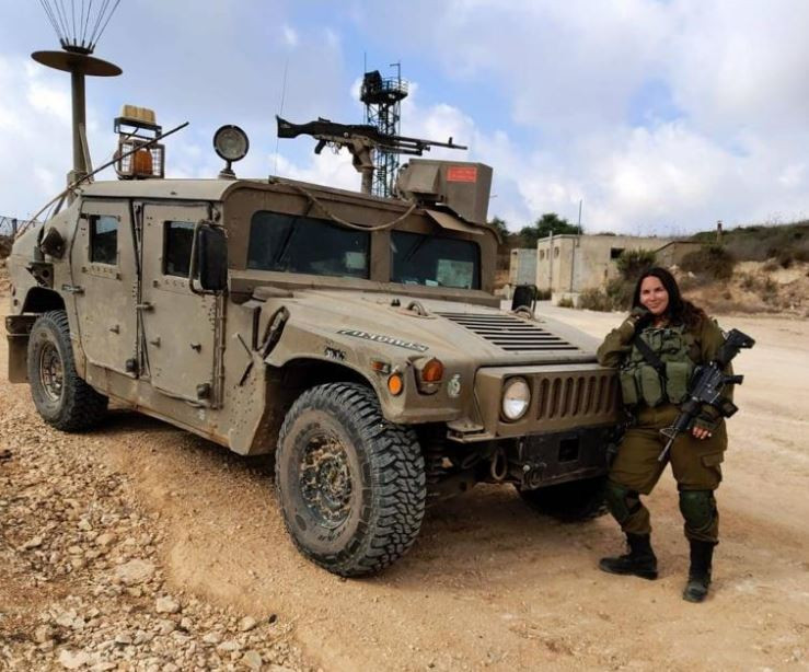An Israeli female combat solider leaning against an armed patrol car