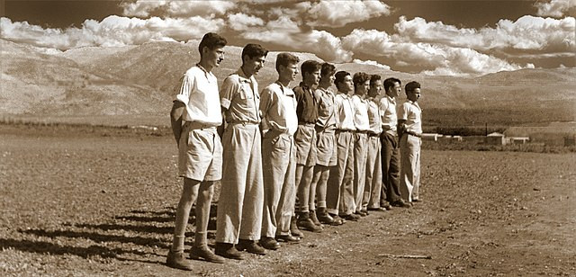Male Palmah fighters lined up in a row with their hands behind their backs outside in the desert