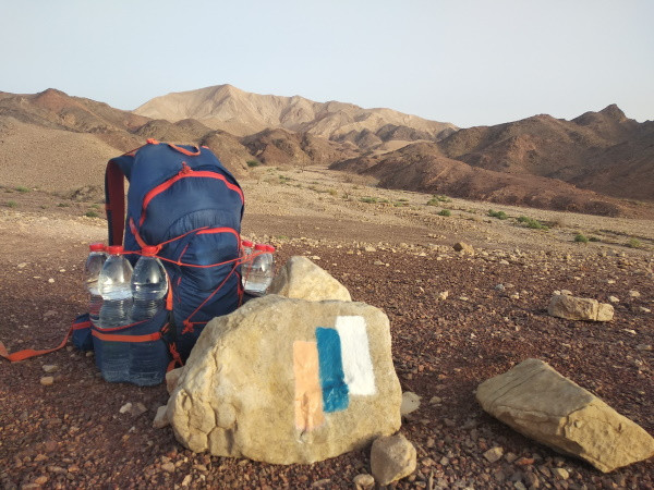 A backpack next to a rock with a Shvil Yisrael symbol in the desert