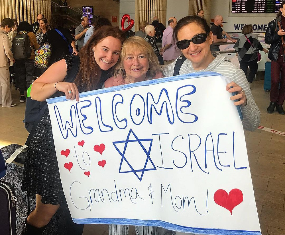 Barbara Gordan at Ben Gurion airport with her daughter and granddaughter, Becca with a 'Welcome to Israel' sign