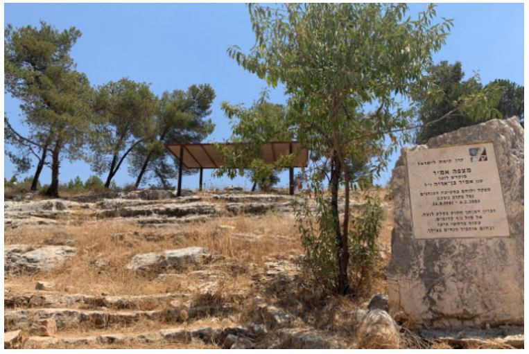 A sign embedded in a rock with details on Mitzpeh Amir with a pergola in the background.