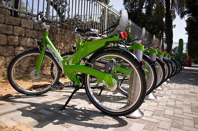 A row of green Tel-Avon bikes for renting parked along a wall in Tel Aviv