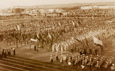 The opening ceremony of the first Maccabiah Games with rows of people lines up and holding flags