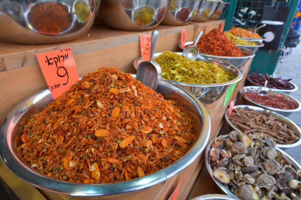 Large open bowls of colorful spices lined up for sale