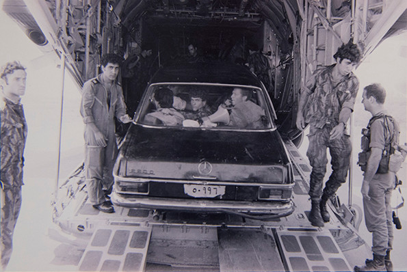 A Mercedes filled with Israel Israeli soldiers backing down an airplane's ramp.