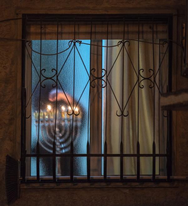 A hanukkiah being lit behind a closed window