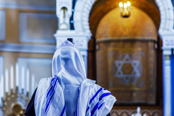 Man wearing a blue striped tallit while facing the ark inside a synagogue