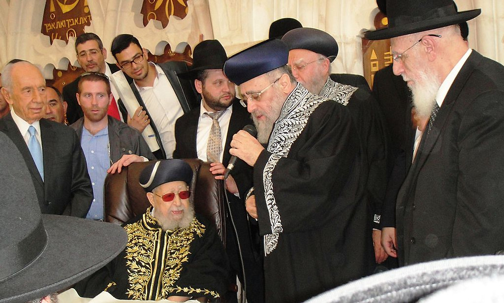 Rabbi Yitzhak Yosef giving a speech with a microphone next to Ravvi Ovadia Yosef sitting in a chair in a crowded room.