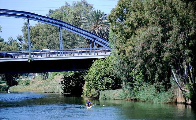 The Yarkon River with a person on a kayak in the water going under a bridge
