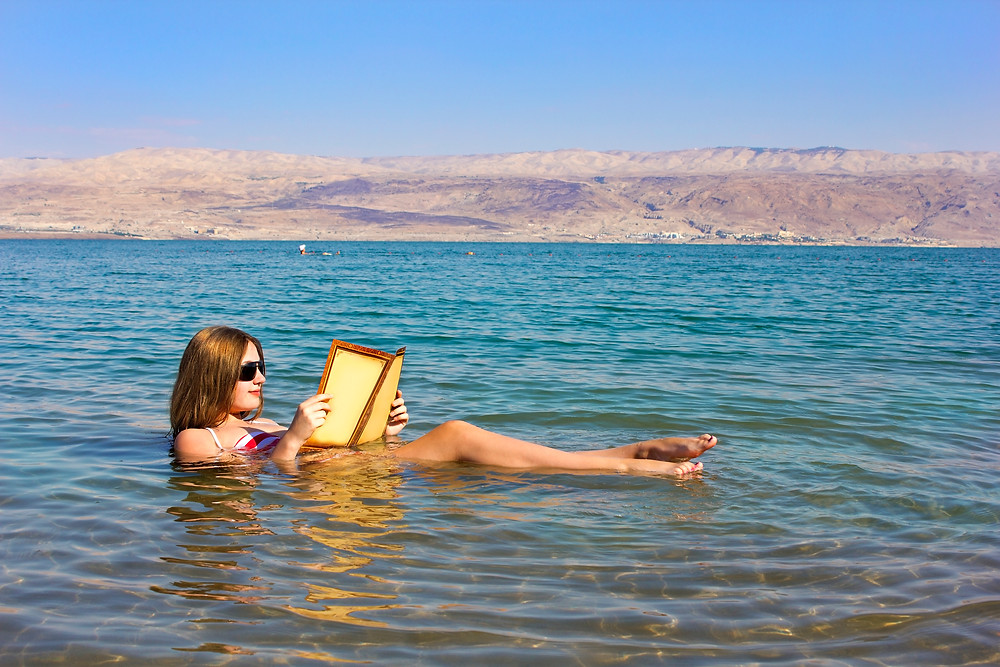 A young woman reading a paper while floating in the Dead Sea
