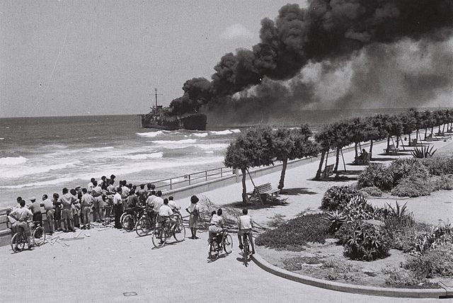 The Altalena ship at sea burning with black smoke while a crowd of onlookers watch from a path on along the shore