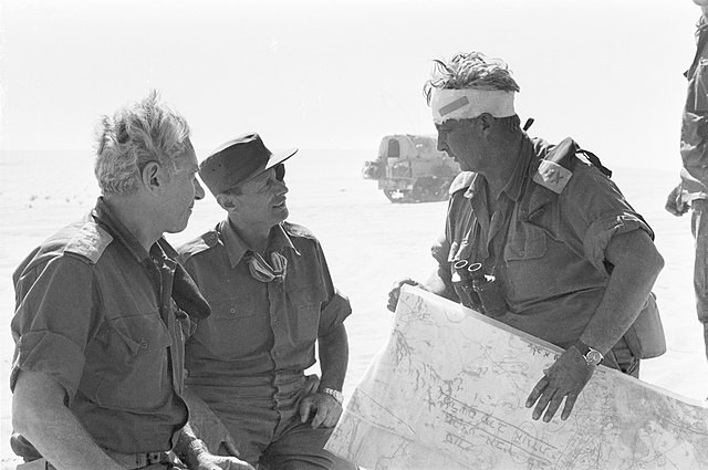 """General Ariel Sharon holds in his hand the map of Operation """"Knights of the Heart""""."""