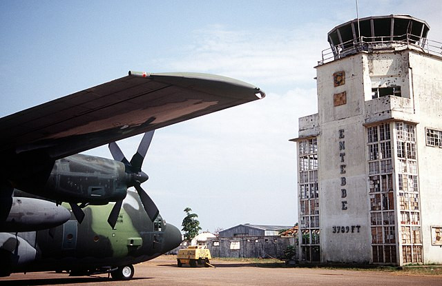 """Entebbe terminal with a U.S Hercules parked to the left and the old terminal building to the right with the words """"Entebbe"""" down the side."""
