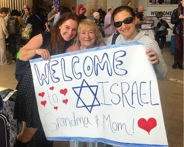 """Becca, her grandmother, and mother holding up a sign that reads """"Welcome to Israel Grandma & Mom!"""""""
