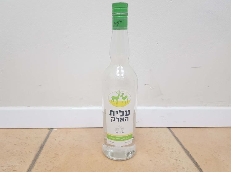 A half full bottle of Elit Arak placed on the floor