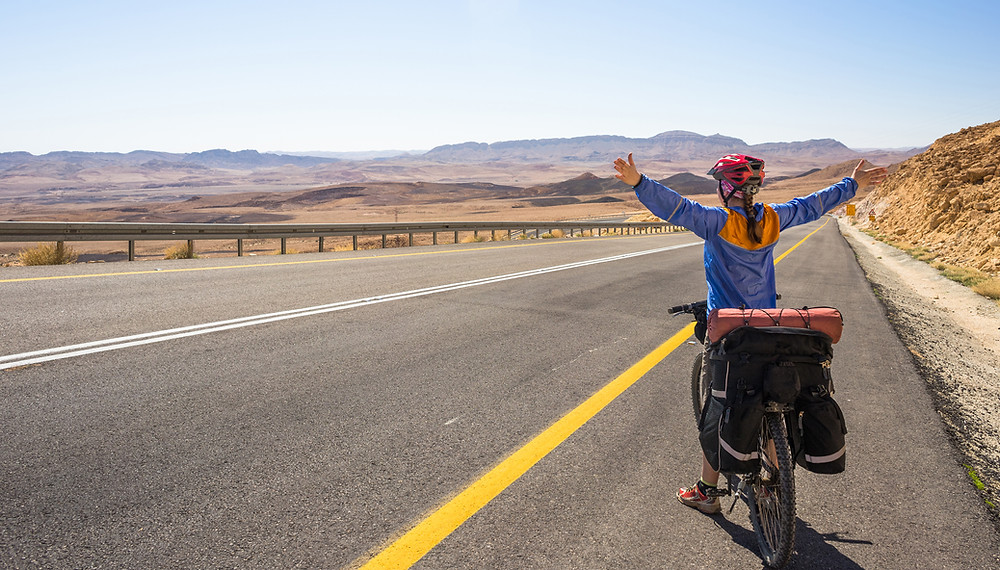 A bicyclist on the side of an empty road in the desert