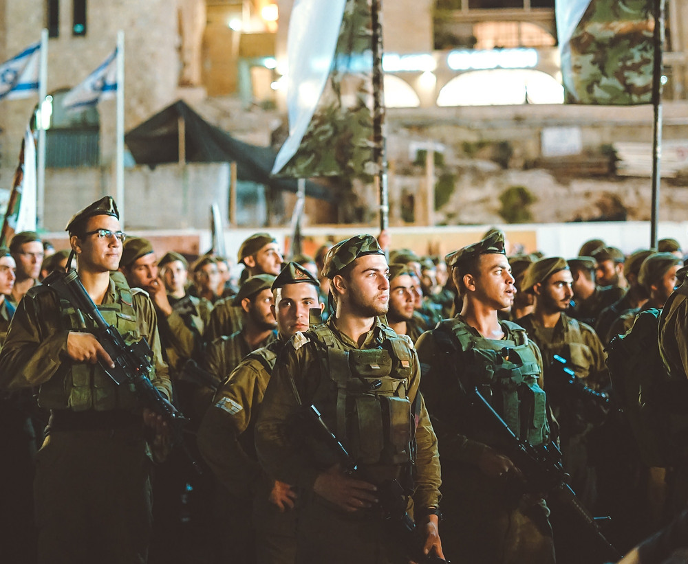 IDF combat soldiers standing to attention at the Western Wall at night