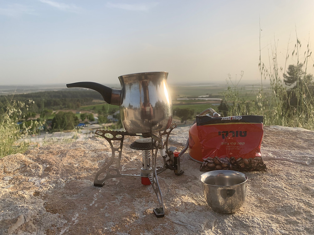 A pakal kafe with a metal cup, bag of Turkish coffee, and a metal pot on a burner on a rock at the Karmei Yosef Lookout