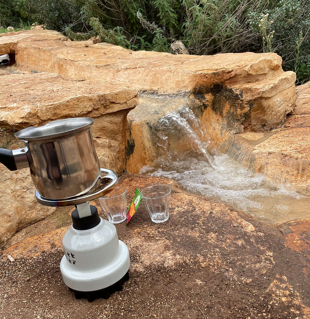 Preparing hot coffee with a pakal kafe at Havat Yair's small waterfall and stream