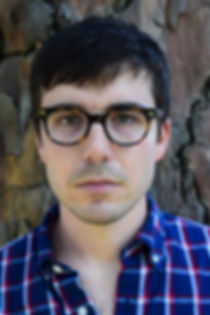 William looks seriously into camera; he is backdropped against a tree, and wears glasses and a blue button down shirt