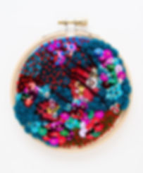 Embroidery hoop decorated with multicolored blue and red felt, yarns, and threads, with colorful sequins and gold beads in clusters