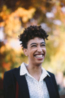 M'Bilia stands outside in front of an autumn tree; she smiles widely at something off-camera, and she wears a white button down with black polkadots under a navy blue blazer