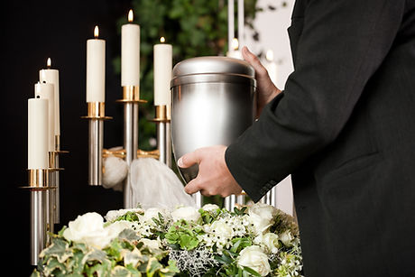 death and dolor  - funeral and cemetery, mortician carrying the urn to a bed of white roses.jpg