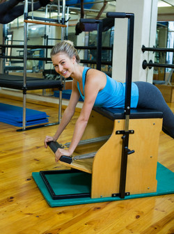 Portrait of beautiful woman exercising on wunda chair in gym_edited
