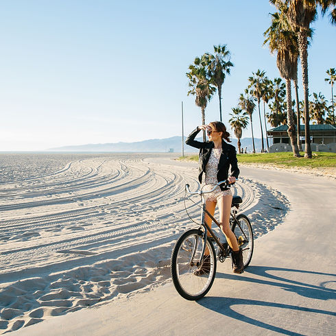 young-woman-cycling-at-beach-looking-out