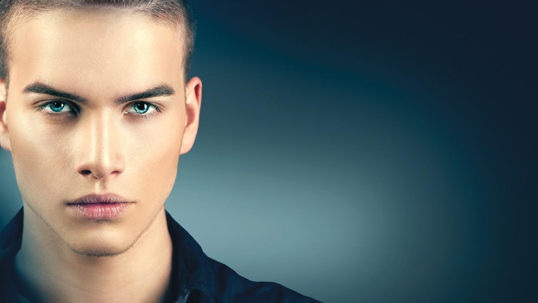 High Fashion model man portrait isolated on dark background. Handsome guy closeup. Stylish haircut,