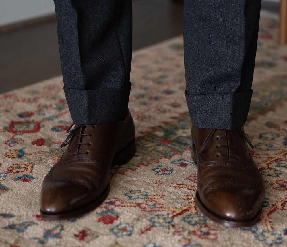Close-up of the cuff on Cavour suit trousers with TLB Mallorca faux wingtips in old english brown
