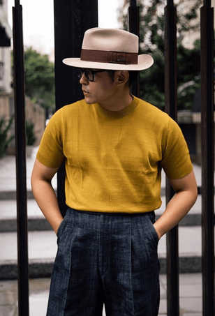 Robert Weng wearing the mustard The Anthology knitted t-shirt with linen trousers